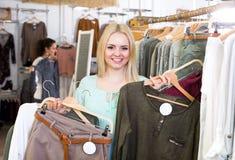 Blonder weiblicher Kunde, der neue Kleider vorwählt Lizenzfreie Stockfotos