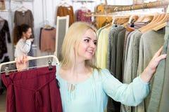 Blonder weiblicher Kunde, der neue Kleider vorwählt Stockbilder