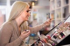 Blonder weiblicher Kunde, der Schönheitsbehandlung in Make-upabschnitt vorwählt Stockfotos