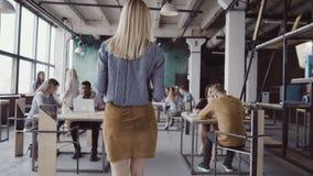 Blonder weiblicher Manager, der durch das Büro und die Kontrollearbeit geht Frau kommt zu den Designern, schaut Gewebebeispiele Stockfoto