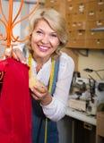 Blonder weiblicher Schneider, der nahe Mannequin in nähender Werkstatt arbeitet Lizenzfreies Stockbild
