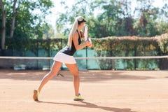 Blonder weiblicher Tennisspieler in der Aktion Ansicht von der Rückseite Lizenzfreie Stockfotos