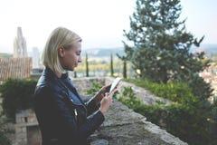 Blonder weiblicher Tourist benutzt Zelltelefon während ihres Spaziergangs draußen in der alten Stadt Lizenzfreie Stockfotos