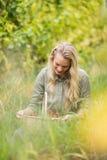 Blonder Weinbauer, der einen Korb der roten Trauben betrachtet Stockfotografie