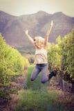 Blonder Weinbauer, der in einen Weinberg springt Lizenzfreie Stockfotografie