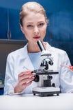 Blonder Wissenschaftler, der mit Mikroskop im Labor, Kamera betrachtend arbeitet Stockfoto