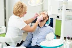 Blonder Zahnarztfachmann gibt einem männlichen Kunden einer modernen zahnmedizinischen Klinik zahnmedizinische Behandlung Stockfotos
