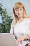 Blondes älteres Frauengraseninternet Lizenzfreie Stockfotos