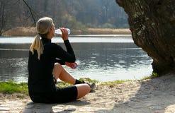 Blondes Athletenmädchen, das auf dem Boden sitzt, um sich zu entspannen, nachdem Trinkwasser unter einem Baum auf einem Seeufer g Stockfoto