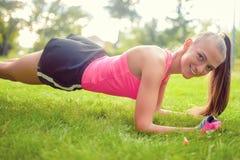 Blondes athletisches Mädchen, das Übungen auf Gras ausdehnt und macht Stockfotografie