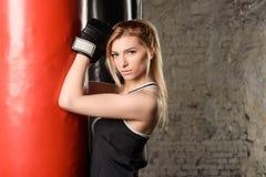 Blondes athletisches Mädchen, das in einer Turnhalle verziert in der Dachbodenart, lehnend auf einem roten Sandsack ausarbeitet Lizenzfreie Stockfotos