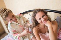 Blondes attraktives Sitzen der jungen Frauen der Freundinnen Lizenzfreie Stockfotos