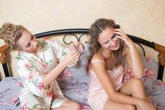 Blondes attraktives Sitzen der jungen Frauen der Freundinnen Stockbilder