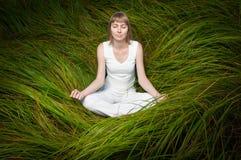 Blondes auf grünem Gras sitzendes und meditierendes Mädchen. Stockfoto
