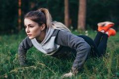 Blondes Ausarbeiten der Junge recht auf Gras im Park, der Knie StoßUPS tut Lizenzfreie Stockfotos