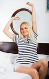 Blondes Ausdehnen in Bett Stockfoto