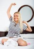 Blondes Ausdehnen in Bett Stockbild