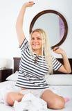 Blondes Ausdehnen in Bett Stockfotos