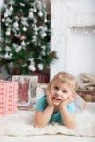 Blondes Baby auf Boden am Baum des neuen Jahres Lizenzfreies Stockfoto