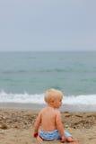 Blondes Baby, das auf dem Strand sitzt Stockbilder