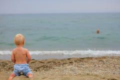 Blondes Baby, das auf dem Strand sitzt Stockfotografie