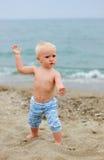 Blondes Baby, das auf dem Strand steht Stockbild