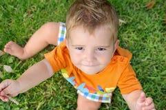 Blondes Baby, das auf Gras mit einem Zweig in seiner Hand sitzt Lizenzfreie Stockfotos
