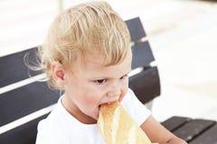 Blondes Baby, das großes französisches Stangenbrot isst Stockfoto
