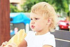 Blondes Baby, das großes französisches Stangenbrot isst Lizenzfreies Stockfoto