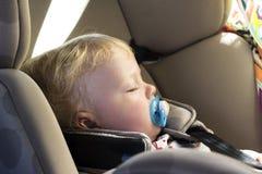 Blondes Baby, das im Autositz schläft Lizenzfreies Stockfoto