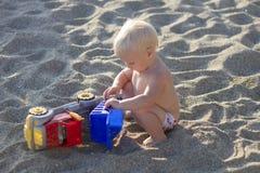 Blondes Baby, das mit Spielzeugauto auf dem Strand spielt Stockfotos