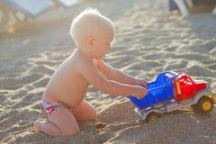 Blondes Baby, das mit Spielzeugauto auf dem Strand spielt Stockfoto