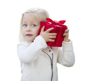 Blondes Baby, das rotes Weihnachtsgeschenk auf Weiß hält Lizenzfreies Stockfoto