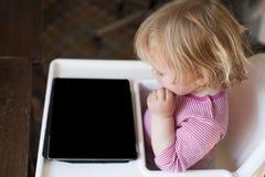 Blondes Baby, das Tablette des leeren Bildschirms betrachtet Stockfotografie