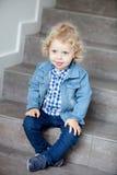 Blondes Baby, das zu Hause auf der Treppe sitzt Lizenzfreies Stockbild