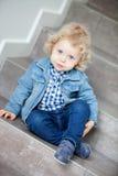 Blondes Baby, das zu Hause auf der Treppe sitzt Stockbilder