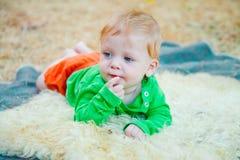 Blondes Baby, das zur Seite schaut Lizenzfreie Stockfotografie