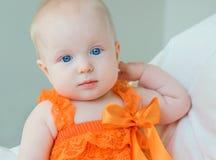 Blondes Baby mit blauen Augen in einem Spielanzug Stockfotografie