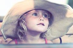 Blondes Baby mit Sommerhut auf dem Strand Stockfoto