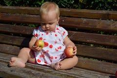 Blondes Baby mit zwei Äpfeln in den Händen Lizenzfreie Stockfotografie