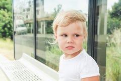 Blondes Baby wartet auf eine Bushaltestelle Stockbild