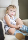 Blondes behaartes blauäugiges kleines Mädchen, das auf Cowboy Boots sich setzt Stockfoto