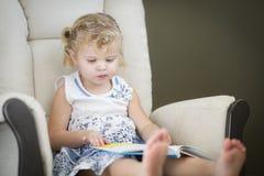 Blondes behaartes blauäugiges kleines Mädchen, das ihr Buch liest Stockbild