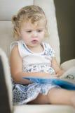 Blondes behaartes blauäugiges kleines Mädchen, das ihr Buch liest Lizenzfreie Stockfotografie