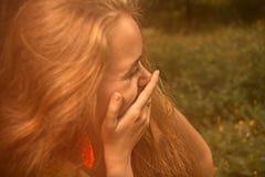 Blondes behaartes Mädchen, das eigenhändig ihr Lächeln versteckt und weg schaut Lizenzfreie Stockfotos