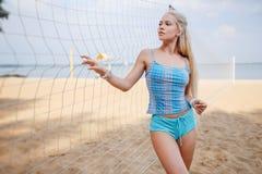 Blondes behaartes Mädchen wirft auf dem Strand in einer blauen Klage auf Stockfotografie