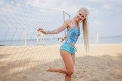 Blondes behaartes Mädchen wirft auf dem Strand in einer blauen Klage auf Stockbilder