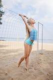 Blondes behaartes Mädchen wirft auf dem Strand in einer blauen Klage auf Lizenzfreie Stockbilder