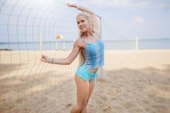 Blondes behaartes Mädchen wirft auf dem Strand in einer blauen Klage auf Lizenzfreies Stockfoto