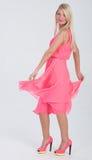 Blondes behaartes Modell im gekräuselten rosa Kleid Stockfotografie